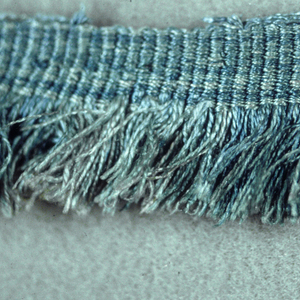 Blue fringe with a plain-woven heading and thread skirt.