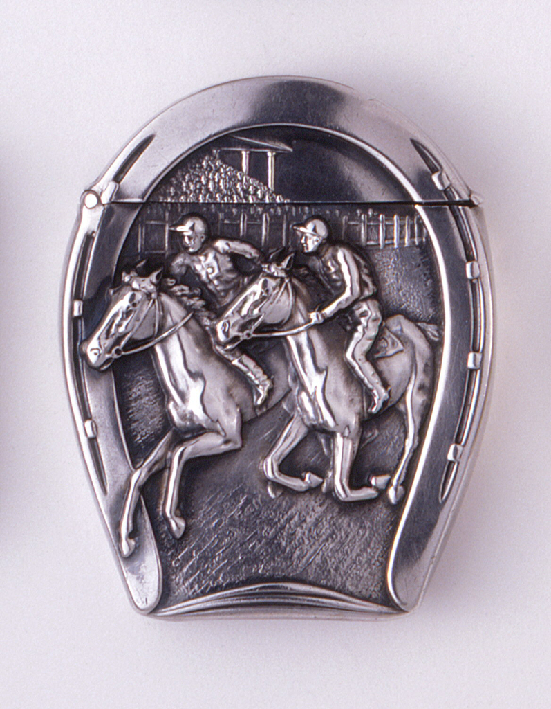 In the shape of a horseshoe featuring central, raised decoration of 2 jockeys racing their horses at track, reverse simulates horse's hoof with shoe. Lid (top of horseshoe) has thumb catch at front and hinged at upper left. Striker on bottom.