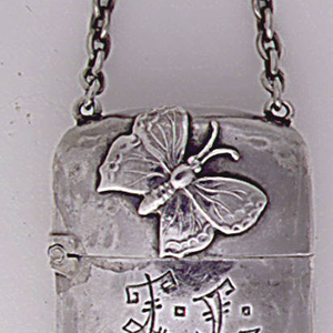 Oblong, with rounded corners and hammered surface. Front features applied sprig of  foliage on body, above which are initials (F. L.?) incised in stylized, Asian inspired font, applied butterfly on lid. Reverse features applied palm fronds on body, applied crab on lid. Chain attached to lid. Lid hinged on side. Striker incised on bottom.