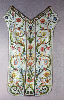 A) front and B) back of chasuble. Central vertical panel in each of straight stem with blossoms, foliage and ribbons. Side panels of serpentine branch with large curling leaves, blossoms and perching birds. Brilliant polychrome silks and gold metal thread, all in laid stitches. Background of silk laid work.