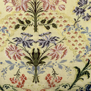 Yellow silk grosgrain brocaded with multicolored silks. Design has serpentine ribbons covered with pink cloverleaves and yellow scalloped edges. Between ribbons are symmetrical floral sprays and delicate branches with pink, blue and purple buds.