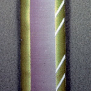 Two pieces of ribbon with a patterned satin border. The first is ombré pale blue with a white border. The second is ombré pale purple with a green and white border.