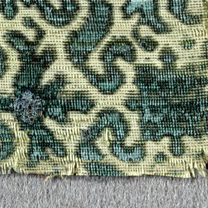 Two fragments of green cut velvet on a cream-colored ground. Small-scale symmetrical design of scrolling ribbons enclosing formal floral motif.