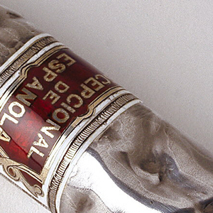 """In the form of a hand-rolled cigar, with red and white enamelled label inscribed """"Escepcional De La Espanola,"""" reverse of label features coat of arms. Last quarter of cigar, where simulated rolled tobacco is visible, flips open as box lid, hinged on reverse. Rolled tobacco at tip likley intended as striker."""