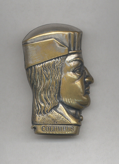 """In the shape of Christopher Columbus' head in profile, identical on reverse. Lid, hinged on side, flips open at bottom when button on neck is depressed,  inscribed """"Columbus"""" on one side of lid, """"Pat.d. Oct.25, '92"""" on reverse side. Striker on bottom of lid."""
