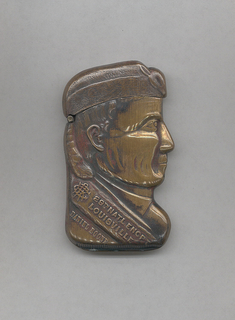 """In the shape of Daniel Boone's head in profile, with racoon hat, and banner draped across shoulder inscribed : """"[unidentified monogram], 29th NATL ENCPT, LOUISVILLE"""" and below """"DANIEL BOONE"""", some red patination on surface, identical on reverse. Hat serves as lid, hinged on side. Striker on bottom."""