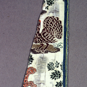 White satin ground, with hunters, dogs, lions, peacocks and trees brocaded in brillian polychrome silks and blue, red and tan chenille.