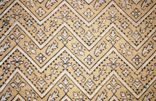 Tan silk with extra wefts of purple and white silk forming horizontal zigzag design with conventionalized floral forms between lines of zigzag. Orphrey, in shape of cross, of deep purple linen stamped with all-over, small-scale blossom and quatrfoil design. Orphrey outlined with ribbon of natural linen and yellow silk.