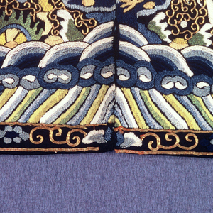 Rank badge for a civil official. Embroidered silk showing a bird facing a sun disk. Ground of clouds with diagonal lines at bottom and scroll border. Seam down the center.