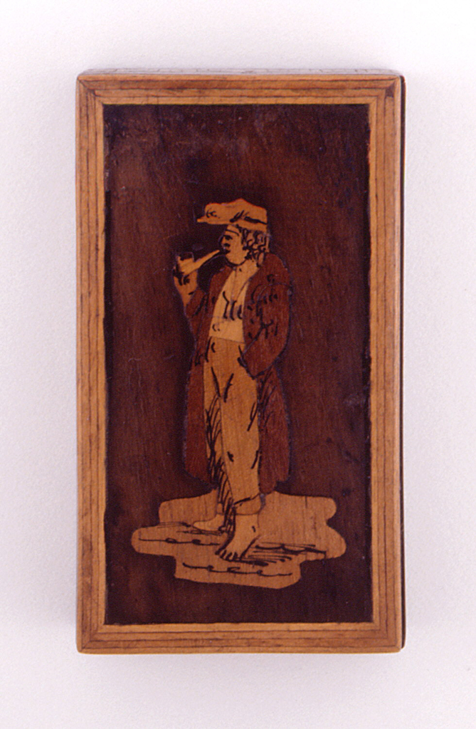 Rectangular, featuring slide-off cover with figure of peasant man in soft cap, long coat, trousers, bare feet, smoking pipe, rendered in dark and light woods with black enamel line drawing, framed in light wood. Sides feature wood mosaic decoration. Large piece of sandpaper adhered to bottom for striker.