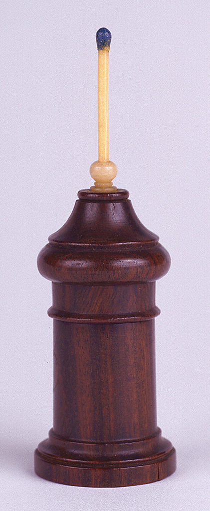 Turned, dark wood, in columnar form, with top that comes to a point, terminating with small, protruding, ivory socket that holds match; turned upper portion of box unscrews to reveal match container; small round of sandpaper adhered to bottom for striker. Round base slightly wider so that box may stand upright on table top.