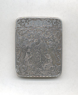 """Rectangular, rounded corners, featuring raised decoration of coat-of-arms, with 2  heraldic, rampant lions flanking shield, inscribed """"HEB"""", on top of which is helmut, overall background of scrolling folliage motifs, reverse identical except shield is unadorned. Lid features cartouche, flanked by scrolling folliage motifs, hinged on side. Striker on bottom."""