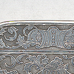 "Rectangular, rounded corners, featuring raised decoration of coat-of-arms, with 2  heraldic, rampant lions flanking shield, inscribed ""HEB"", on top of which is helmut, overall background of scrolling folliage motifs, reverse identical except shield is unadorned. Lid features cartouche, flanked by scrolling folliage motifs, hinged on side. Striker on bottom."