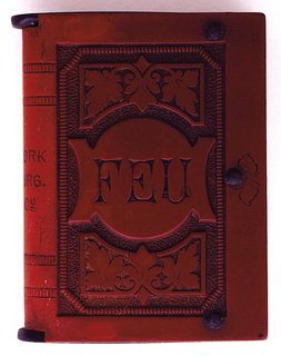 "Rectangular form in design of a book.  Front cover is leaf pattern framing work, ""Feu"" in center. Back cover leaf pattern framing center diagonally inscribed, ""Made in Germany."""