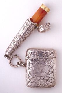 Rectangular, rounded corners, featuring overall engraved foliate scroll pattern, central circular reserve inscribed TM. Reverse side, same decoration, slightly convex. Lid hinged on side, small thumb catch opposite. Striker in recessed groove on bottom. Cylindrical case for cigarette holder attached by rings situated below hinge on box side, similarly engraved with overall pattern and reserve for monogram. At cigarette case top is small, circular lid, with thumb catch, hinged at back. Enclosed is plastic cigarette holder, resembling horn, edged with gold rim.