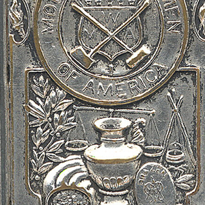 """Rectangular, curved top and bottom, featuring raised decoration, inscribed in circular reserve """"Modern Woodmen of America"""", the center of which displays a shield with a crossed malet and hatchet and monogram """"MWA"""", over circular reserve inscribed """"Pur Autre Vie"""", beneath features an assortment of objects including a scale, urn, and medallion inscribed """"Brazen Coin"""", some foliage motifs interspersed throughout; reverse features male with hatchet raised, chopping a tree trunk, background of trees, cabin, and 2 men on wooden river raft. Lid hinged on side. Striker on bottom."""