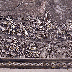 Rectangular, curved top and bottom, featuring raised decoration of biplane in flight over countryside scene with hills, trees, and houses in background; reverse features stylized floral and leaf frame, beneath which is piece of celluloid, and empty reserve. Lid hinged on side. Striker on bottom.