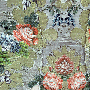 Part of a chasuble with a design of a central palmette, flowers and foliage in shades of red, blue, green on a silver background. Some leaves in gold. Piece has gold lace trimming.