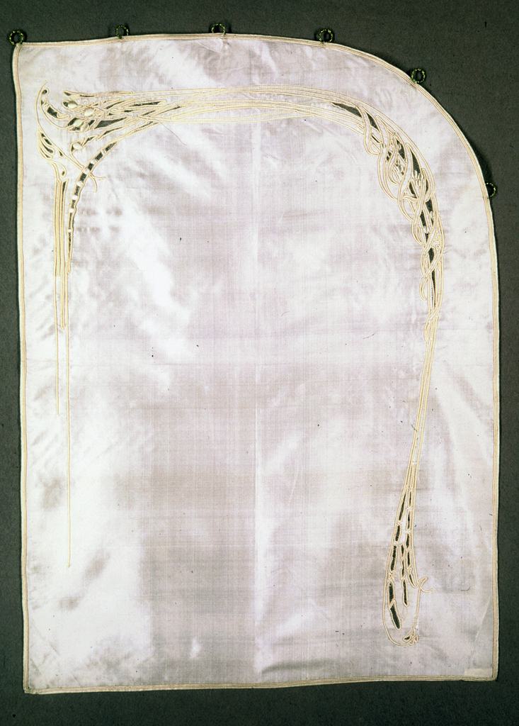 Pair of short curtains of cream colored silk, embroidered in silk of same shade. Long thin lines of attenuated design, vaguely leaf-like in upper heavier sections; worked around net insertion. Curved at upper corner, at one side, and fitted across curve with small brass rings.