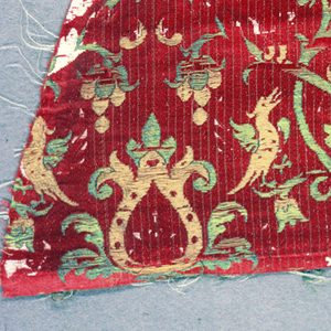 Allover design of stylized leaf motifs and birds in yellow and green on a red ground.