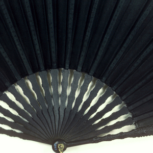 Pleated fan. Black organdy leaf. Guards and sticks of black wood, delicately carved on obverse with all-over flower and scroll motifs. Guards also decorated with a cartouche incised with quatrefoil and trefoil motifs. Box covered with maroon imitation leather with gilt tooling, marked: Tiffany & Co. Made in France