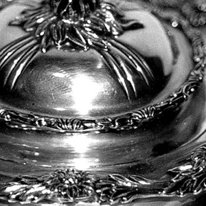 """Squat globular form engraved with foliate monogram """"RMA"""", with reeding, wavy rim, two squared, curved horizontal handles with foliate decoration; base with four foliate feet; domed and reeded lid with flower bud knop."""