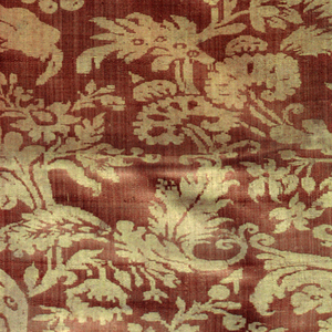 Pattern of free floral serpentines closely covering ground; in golden yellow cloth weave on pale salmon warp twill ground.  Three kinds of selvages on different breadths - green chevron warp twill; green and white warp twill with cloth edge;  gold warp twill.  Pink and yellow silk fringe of period.  Lined with cotton weft twill.