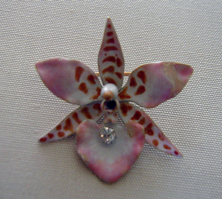 "Enameled gold brooch in the shape of an six-petal orchid with diamons in the center of ""flower."""