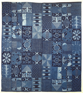 Adire textile with a checkerboard of rectangles, each filled with pattern reserved in white on a deep indigo blue ground. The patterns include checkerboards, lattices, herringbones, pinwheels, trees, flowers and leaves, and other unidentifiable figural forms. The textile is composed of two widths of fabric stitched together in the center; the two pieces are identical in their patterning, but have been arranged in opposite orientations.
