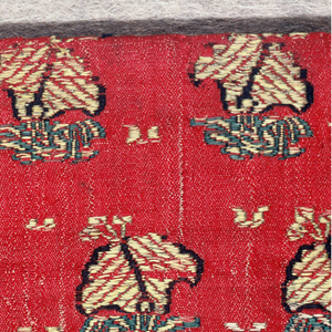 Red satin brocaded in small scale flower design arranged in horizontal rows, the blossom tilted in alternate direction in alternate rows. Colors yellow, outline din dark blue, green for leaves. Cord: worn. Received as trimming borders for table mats made from  1966-30-3 & 1966-30-8a