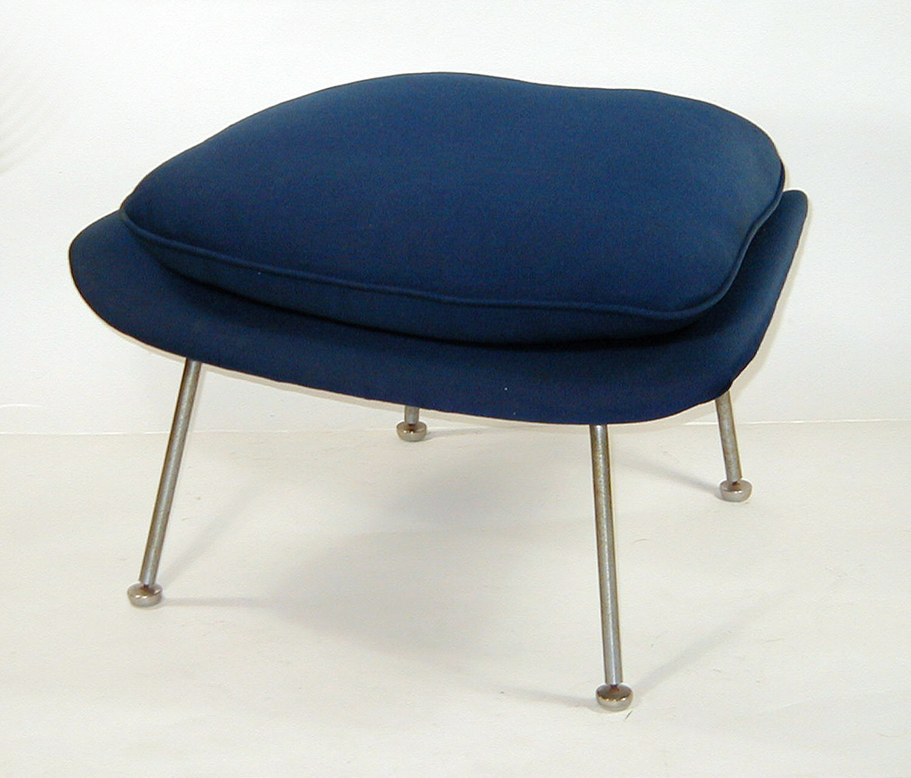"""Blue, open, shell-like chair upholstered in fabric, resting on chrome legs.  The chair's armrests formed by symmetrical """"dips"""" in the shell.  Accompanying ottoman, also with chrome legs and a rectangular, blue, cushion."""