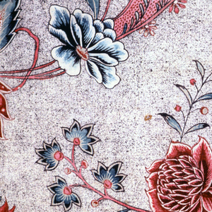 Floral design with large exotic blooms in reds and blue, on a black speckled ground.