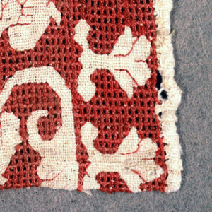 Four fragments of a band with a repeating pattern of a curved vine in reserve on a natural colored ground with a red embroidered background.