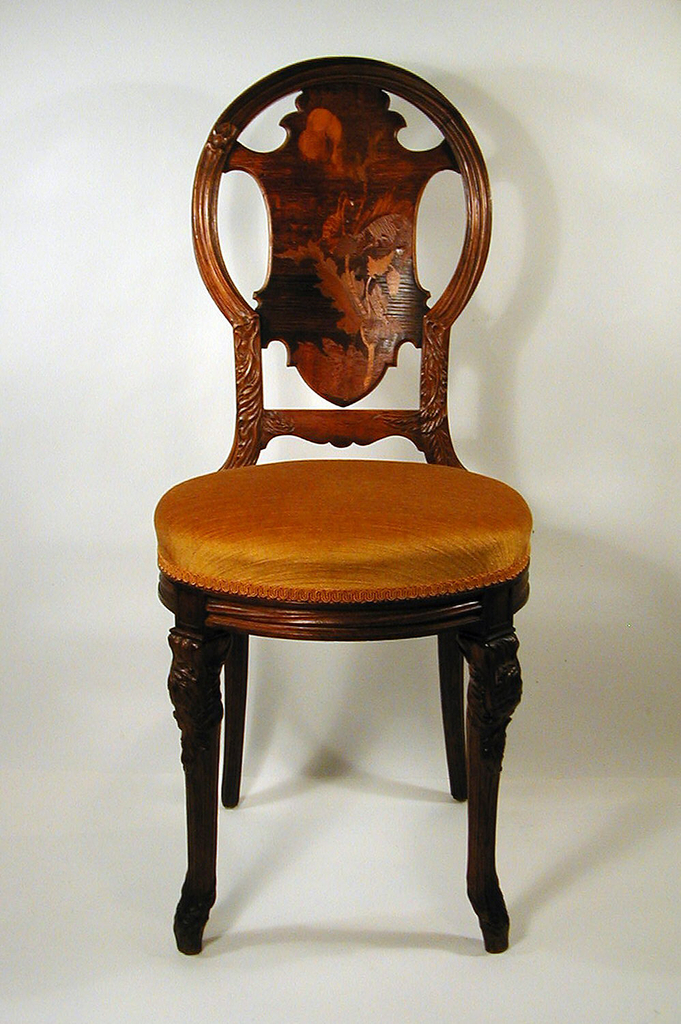 Side chair with rounded back rail, upholstered yellow seat, and rounded seat frame.  Four tapered legs, of which frontal legs emulate natural forms in engraving at top.  Floral and leaf-like motif on the seat back.