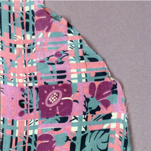 Back of a blouse with an open plaid of yellow and orange lines of varied widths, overlaid with a floral pattern in green and pink. (b) is alternate colorway.