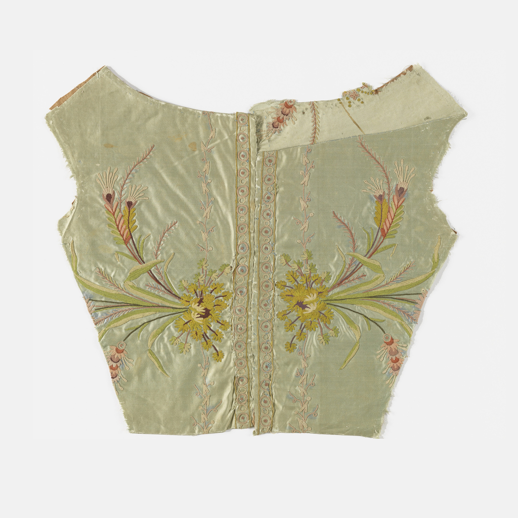 Bodice back with a repair at the upper right shoulder. Pale greeg silk satin embroidered in colored silks using chain stitch. Sprays of flowers and wheat project sideways from the center back. Borders of conventionalized flowers with dots and rings down either side of center back seam. Backed with tan linen.
