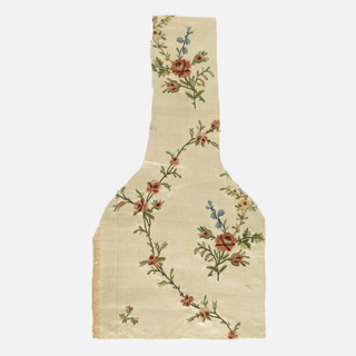 Shaped fragment of white satin is embroidered in colored silks and chenille yarns with a design of floral sprays enclosed by flowering vines.
