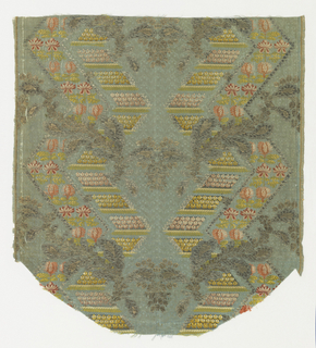 Textile fragment with faded blue ground figured with pattern of ogee arches and clusters of three dots. Brocaded with design of large vertical zigzags outlined by minute ornaments in silver yarns and containing a large variety of flower forms in polychrome silks.  The zigzags are interrupted by undulating branches in silver thread.