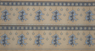 "On a tan ground, abstract ""adobe""-like stepped shapes in blue and dark gray with crosses, bordered by crosses on a gray ground. Printed two borders across the width."