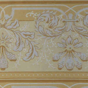 On tan ground, gray vines and white rinceaux in scrolls. Printed two borders across the width.