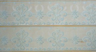 On light pink ground, in two registers, row of scroll motifs in light blue with white laurel-like plant forms.