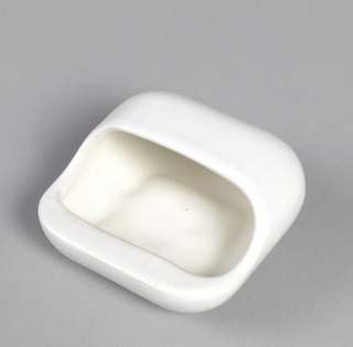 "White glaze. Molded. Ashtray is square, with sides that curve inward toward base. Curved sides continue on half of upper body to create ""pocket"" with curved opening and flanged cigarette rest at front."