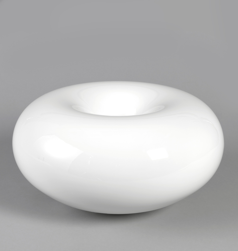 Low, thick, glossy white bowl-like form with circular slit at the bottom of the center depression, for the discharge of steam.