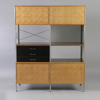 four dimpled plywood sliding panels on top and bottom two sections, the left side with three drawers of black lacquered wood, and metal handles, with lacquered Masonite panels in shades of taupe, beige and grey, the second level with angled braces on the left, and perforated aluminum panel on the right.