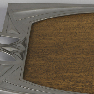 Of almost rectangular form with wood surface surrounded by pewter border with pierced and raised handles,