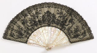 Pleated fan with black lace leaf showing cupids, flowers and Rococo Revival scrolls on white silk satin. Plain mother-of-pearl sticks
