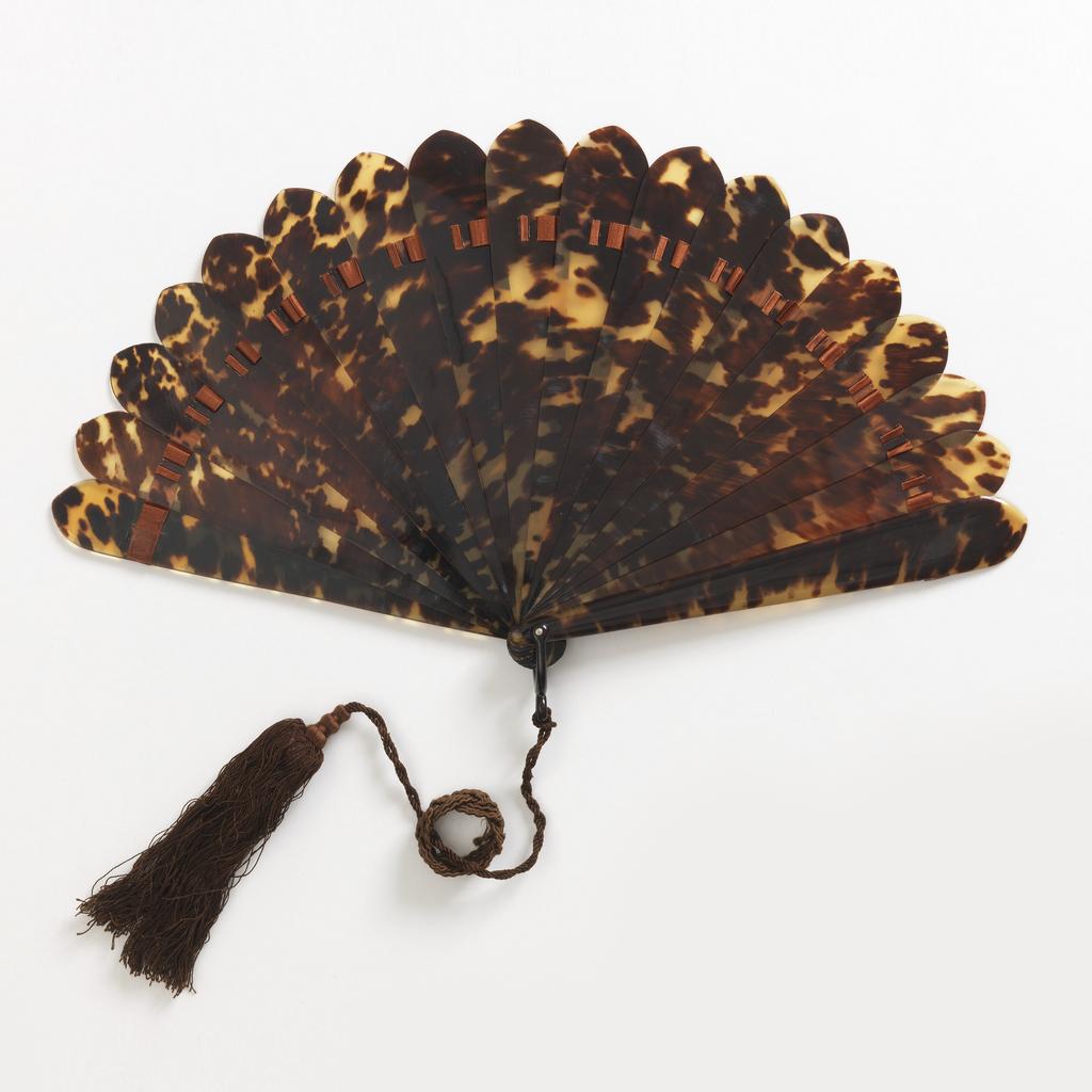 Brisé fan with tortoise shell sticks. Brown silk tassel, metal pin