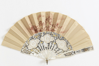 Pleated fan. Double taffeta leaf. Obverse painted in red ochre monochrome a scene of cupids. Reverse: plain. Sticks: mother-of-pearl, carved à jour, silvered and gilded.