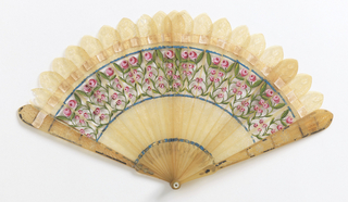 Brisé fan. Bonesticks carved à jour, gilded on reverse. Obverse painted. Designs of roses in red and green, with blue borders. Cardboard box covered with paper showing blue fleur-de-lys.