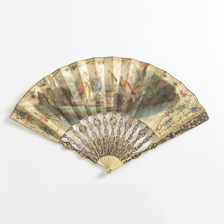 Pleated fan with painted skin leaf. Obverse: scene of shepherd and shepherdesses at a well.  Reverse: sprays of flowers.  Ivory sticks carved à jour, gilt and silvered. Pin is set with a brilliant at each end.